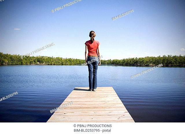 Mixed Race woman at the edge of dock at lake