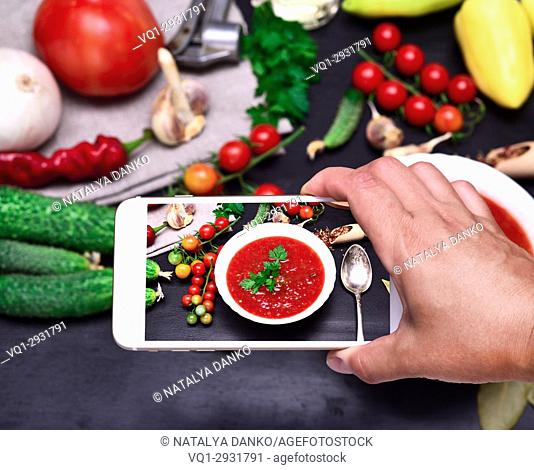 smartphone in the human hand, the process of photographing gazpacho soup with fresh vegetables, close up