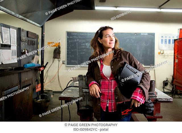 Female metal work teacher leaning against classroom workbench