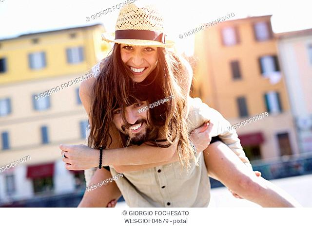 Portrait of happy young man giving his girlfriend a piggyback ride