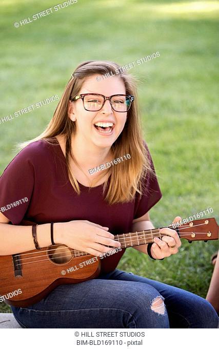 Student playing ukulele on college campus