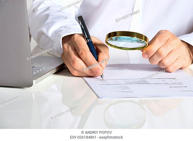 Midsection of businessman analyzing invoice with magnifying glass by laptop at office desk