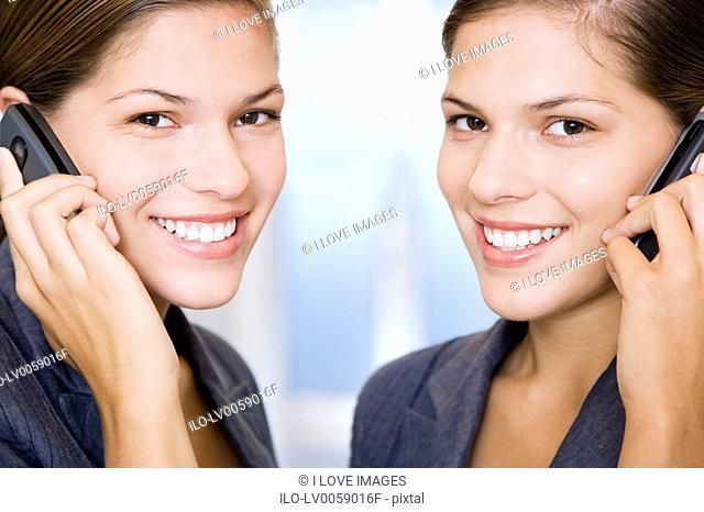 Two identical twin businesswomen using cellphones