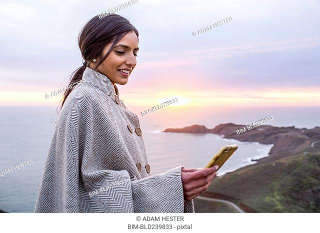 Smiling Indian woman texting on cell phone near shore