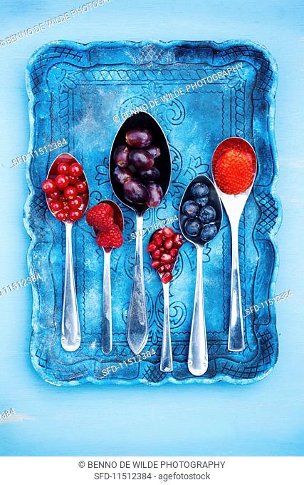 Various berries and pomegranate seeds on spoons
