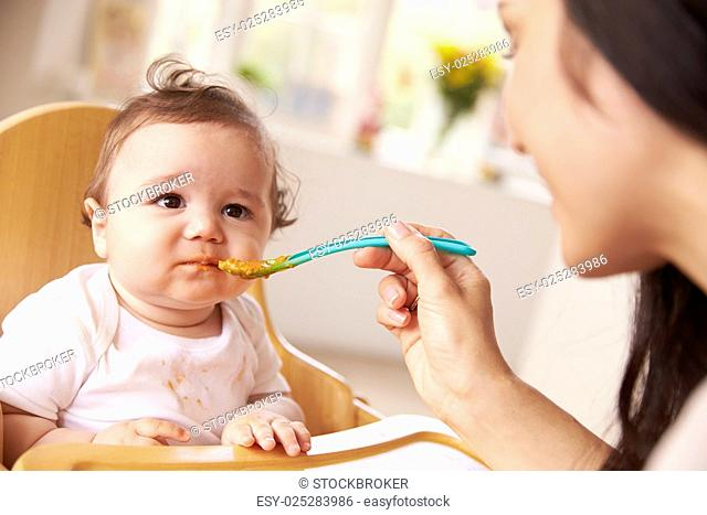 Happy Baby Being Fed In High Chair At Meal Time