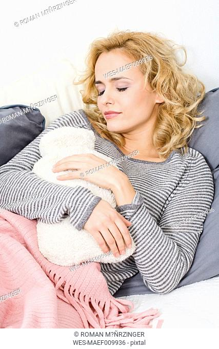 Woman lying on couch with hot water bottle