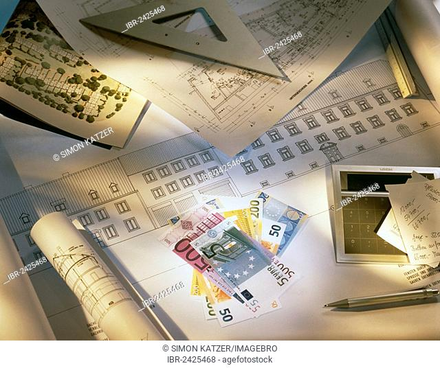 Documents and plans for the construction of a house lying on a table alongside euro banknotes