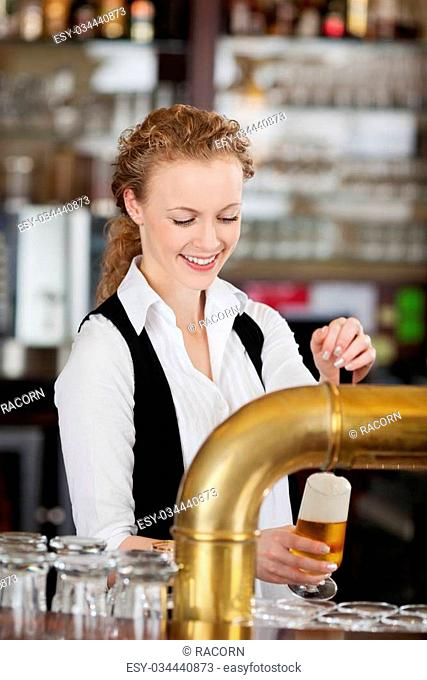 Happy barmaid pouring draft beer standing behind the counter in a bar or pub filling a pint glass