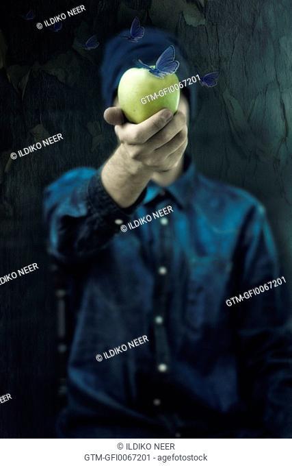 Man holding an apple with butterflies