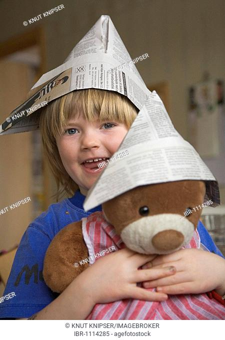 4-year-old girl holding a teddy bear, both wearing a newspaper hat