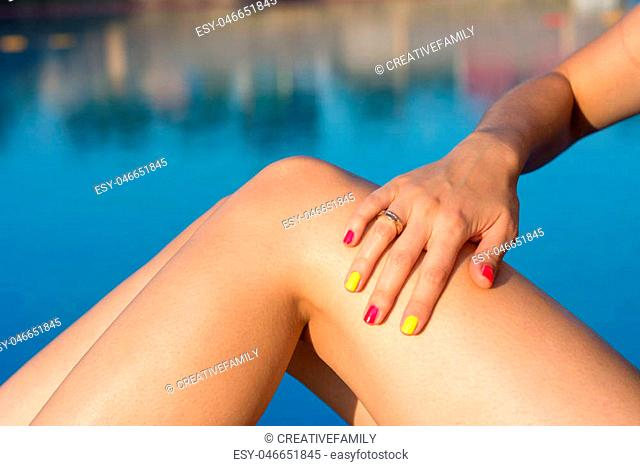 Woman applying sun lotion by the swimming pool