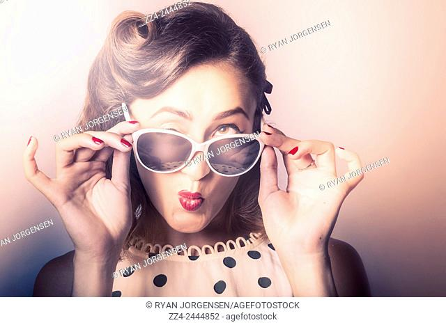 Fun comical retro fashion portrait of a beautiful girl in sunglasses pulling a funny face close-up. Pin-up pout