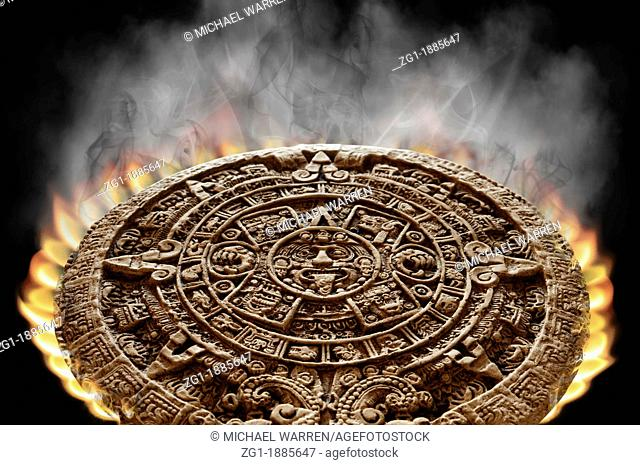 Apocalyptic Mayan Calendar on fire with smoke rising from its surface on a black background