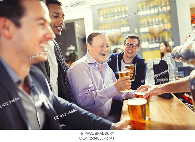 Smiling men friends drinking beer at bar