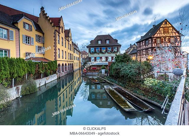 Dusk lights on houses reflected in river Lauch at Christmas Petite Venise Colmar Haut-Rhin department Alsace France Europe