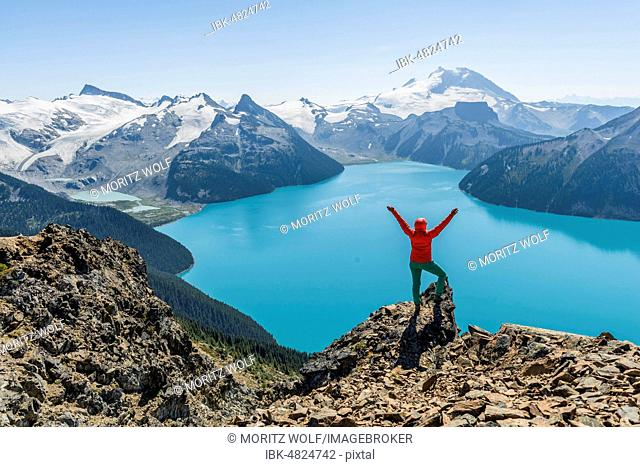 View from the Panorama Ridge hiking trail, hiker on a rock stretches arms into the air, Garibaldi Lake, Guard Mountain and Deception Peak, back glacier