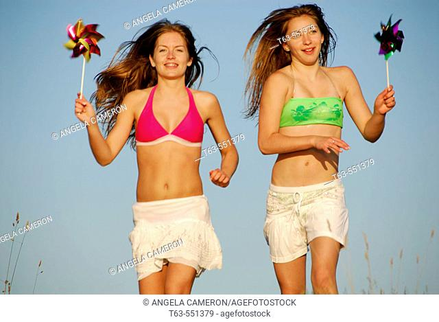girl 13, girl 18 yrs running with pinwheels at the beach