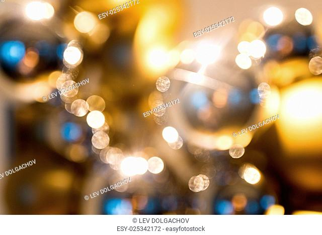 holidays, luxury and background concept - blurred golden christmas decoration or garland of beads or balls bokeh
