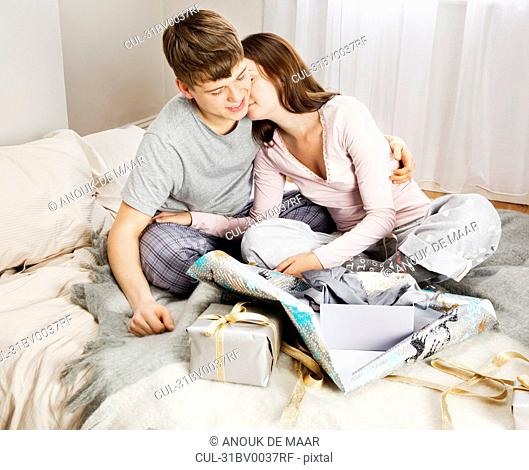 Couple embracing and unpacking presents