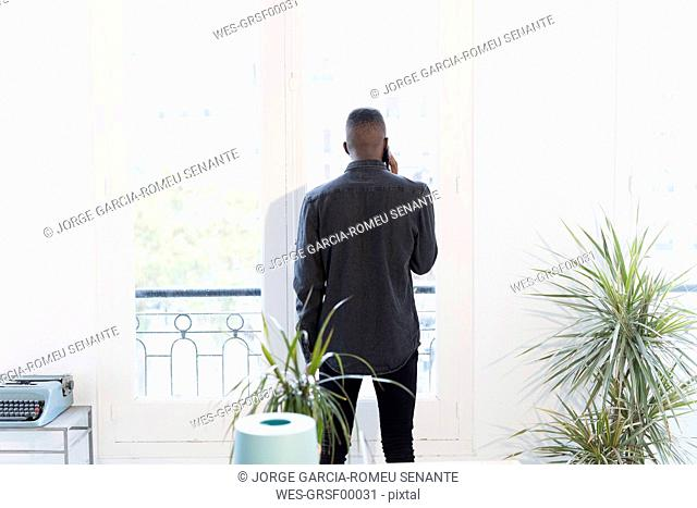 Back view of businessman on the phone in the office looking out of window