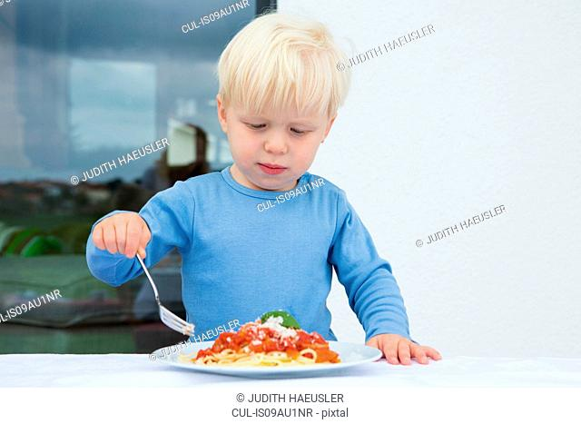 Male toddler eating spaghetti on patio