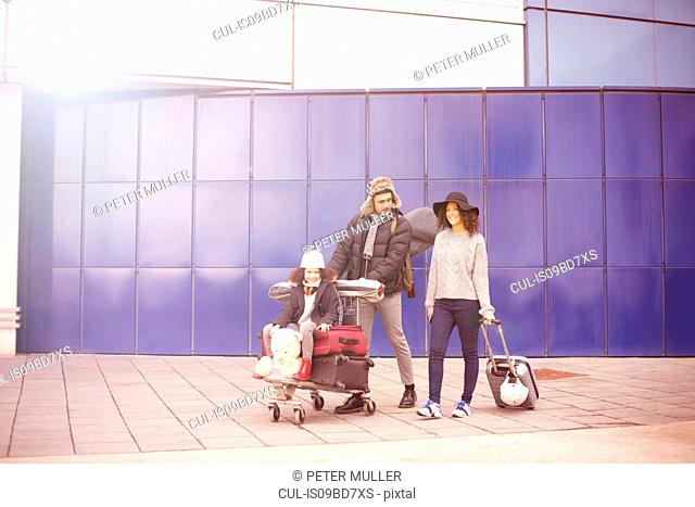 Girl with parents riding on luggage trolley