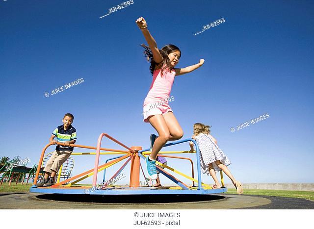 Children jumping off merry-go-round at playground