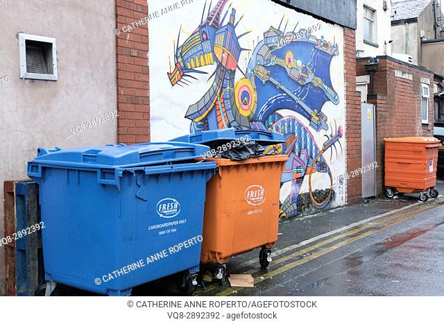 Dragon street art grafitti with orange and blue bins in Blackpool back street, England, UK