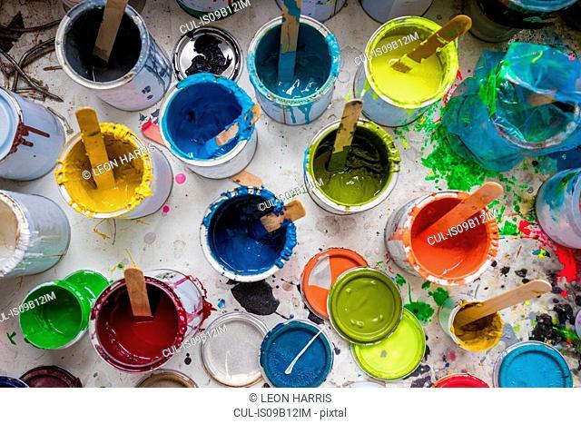 Overhead view of stirrers in paint pots in surfboard maker's workshop