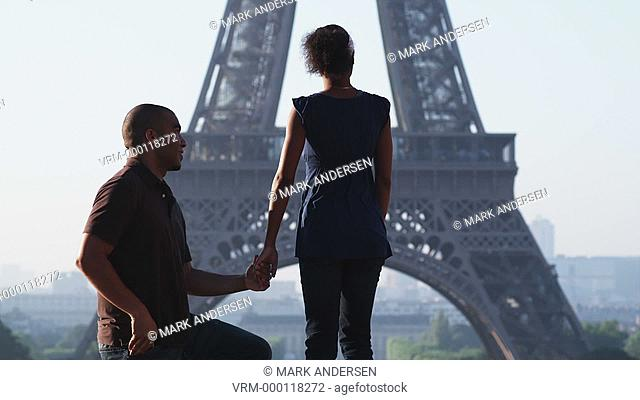 man proposing marriage to woman in front of the Eiffel tower