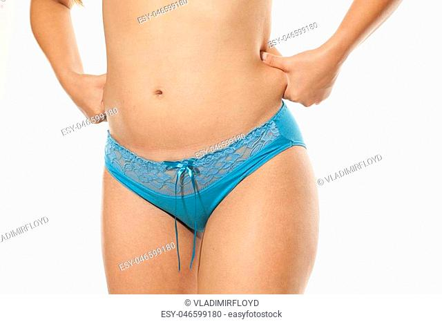 young woman pinching her fat on her waist on a white background