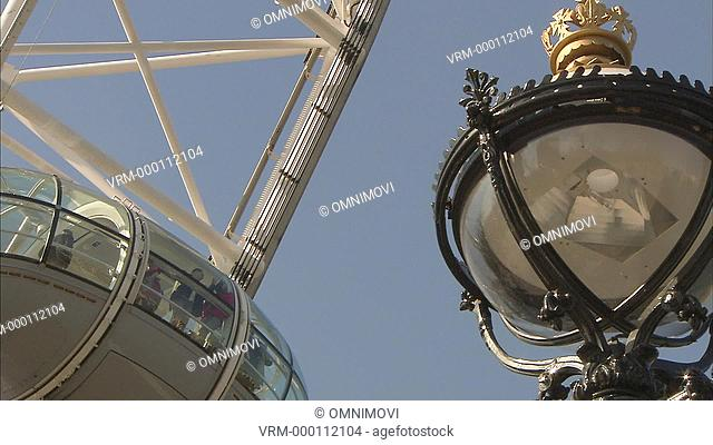 Tourists inside London Eye Pod, lamppost in the foreground