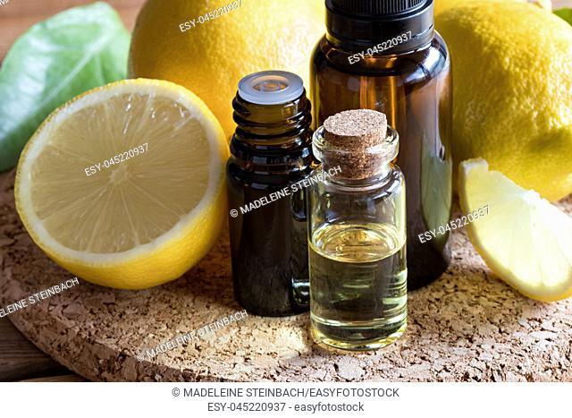 Bottles of lemon essential oil with fresh lemons in the background