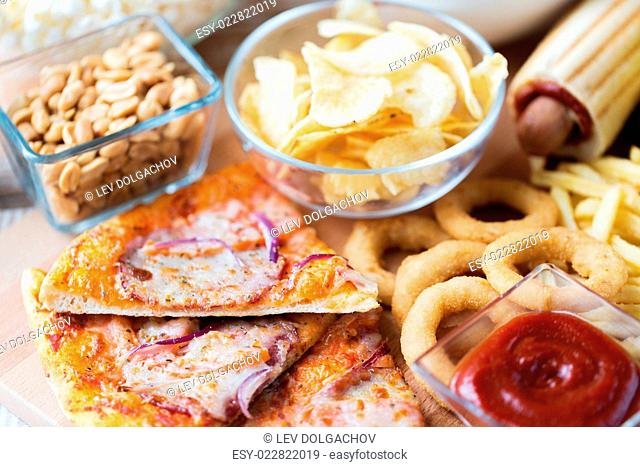 fast food and unhealthy eating concept - close up of pizza, deep-fried squid rings, potato chips, peanuts and ketchup on wooden table top view