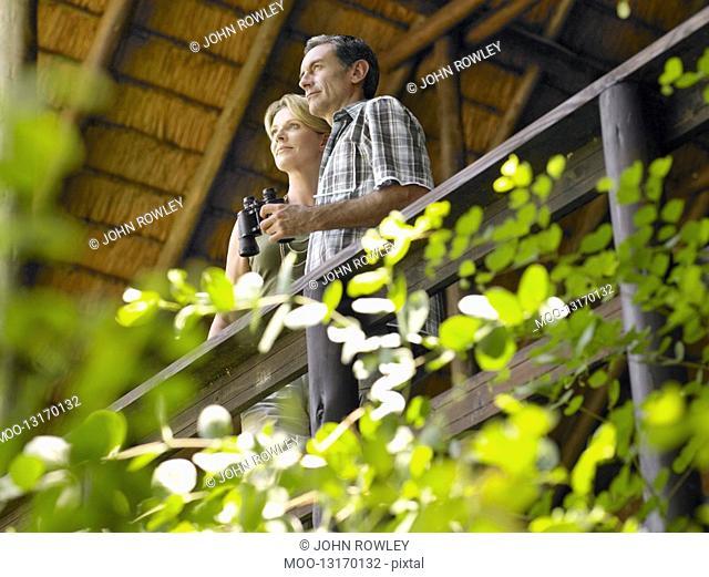 Couple on terrace man holding binoculars low angle view
