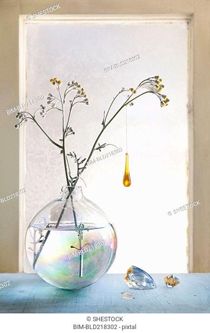 Glass ornament hanging from plants in glass vase