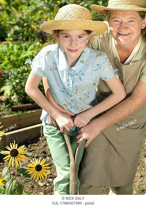 A mother and daughter work in a garden