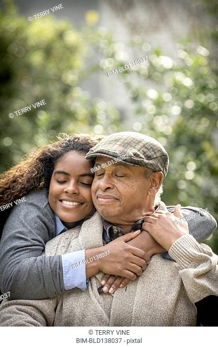 African American woman hugging father outdoors