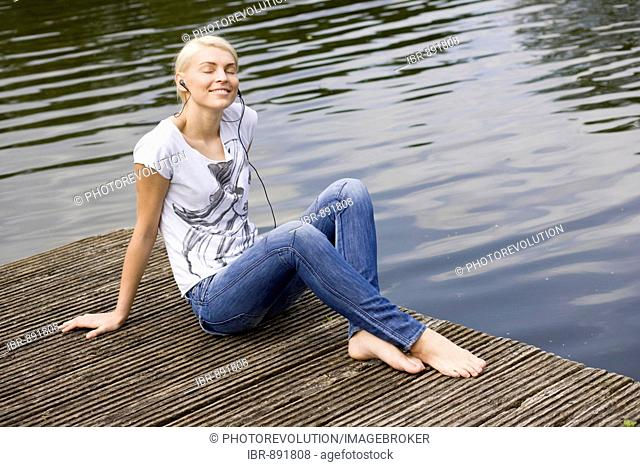 Smiling young blonde woman sitting on a wharf at a lake and listening to music