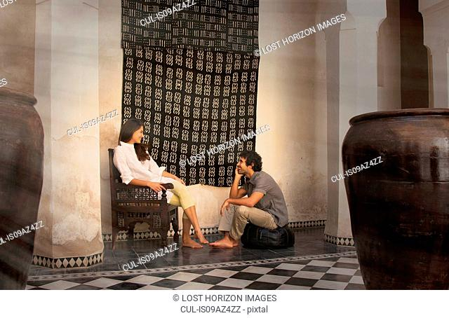 Young couple sitting on chair and pouffe chatting, Marrakesh, Morocco