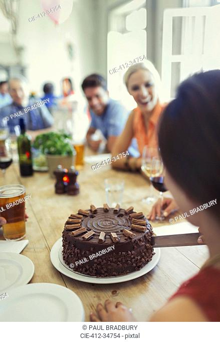 Woman cutting chocolate birthday cake with friends at restaurant table