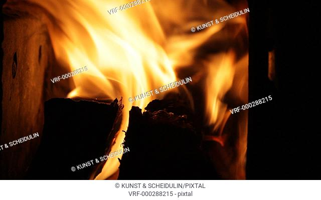 Logs are burning merrily in a fireplace. Red glow, black logs and yellow-white flames. Västernorrlands Län, Sweden