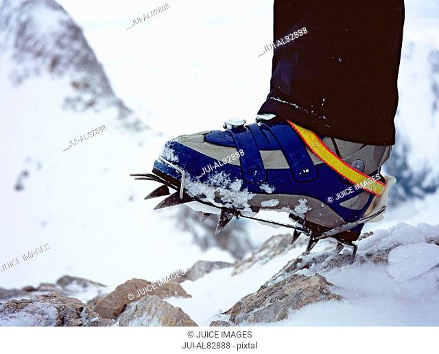 Close up of hiker's shoe with crampon on snowy mountain