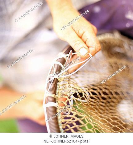 A man repairing fishing tackle