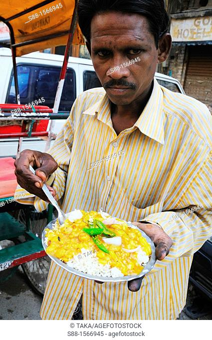 Man eating beans curry for breakfast on the street