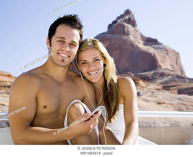 young couple at the lake listening to an ipod together