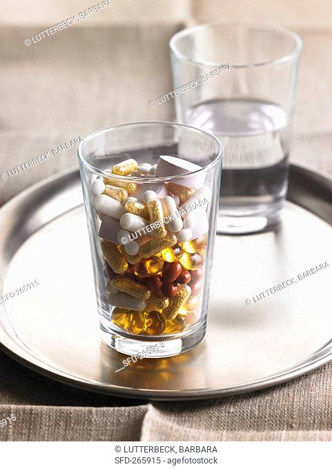 Glass of assorted capsules & tablets in front of glass of water