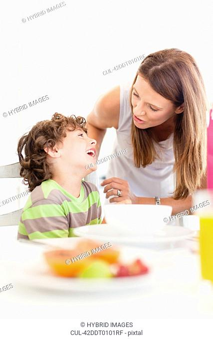 Mother talking to son at breakfast