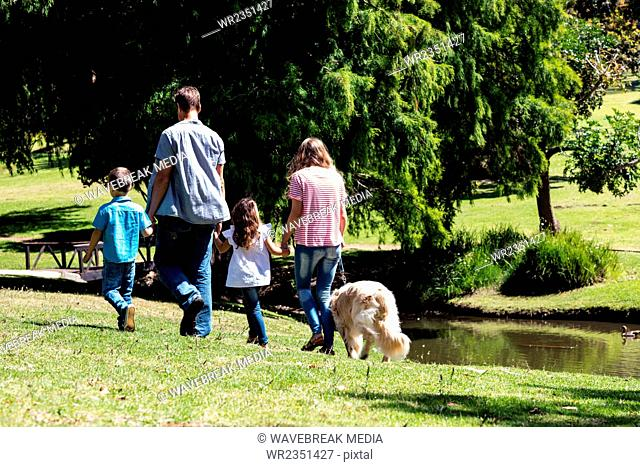 Family walking in the park with their dog